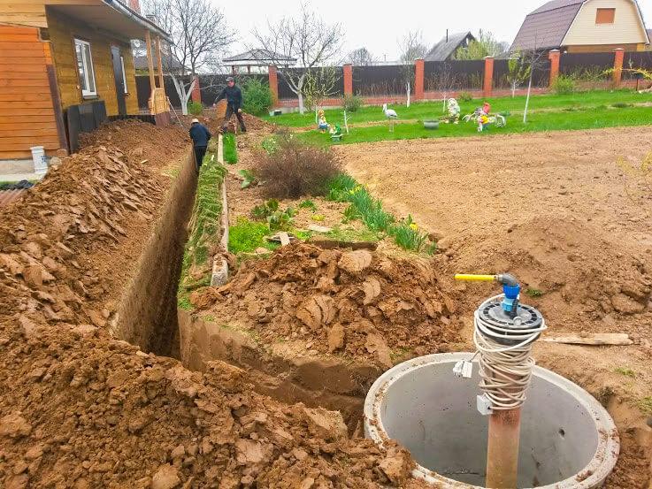 Рабочие делают водопровод к дачному загородному дому